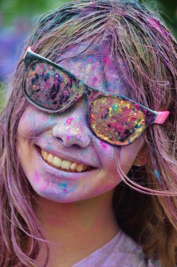 Girl in Black Framed Sunglasses With Color on Her Face from Color Run Smiling