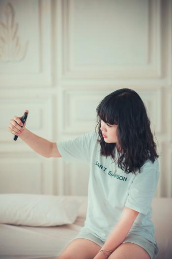 Girl in Blue Crew Neck Shirt Using Her Mobile Phone Indoors