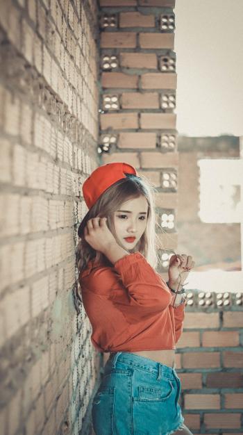 Girl in Orange Top Near Brown Concrete Brick