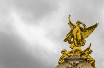Gold Angel Statue Under Grey Clouds