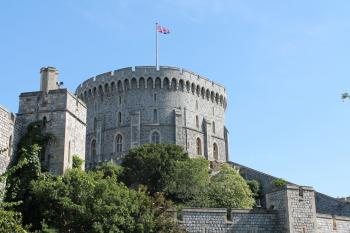 Gray Concrete Castle With Flag on Top Under Blue Sky