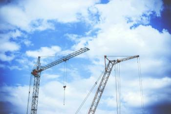 Gray Rectangular Power Crane With Blue Cumulus Clouds Above As Background during Daytime