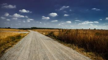 Gray Road in Between Brown Grass Under White Cloudy Sky