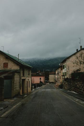Gray Road Surrounded With Concrete Houses With Background of Dark Clouds