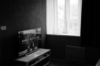 Gray Scale Photo of Flat Screen Tv on Top of Wooden Tv Rack