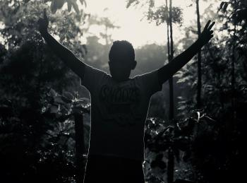 Gray Scale Photo of Man in White Shirt Raising His Hand Near Plants