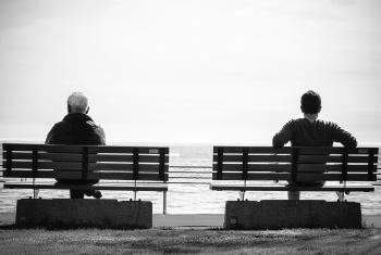 Grayscale Photo 2 Person Sitting in a Separate Benches on the Seaside