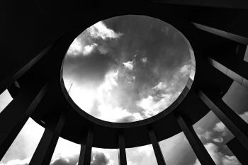 Grayscale Photo of a Round Building With Hole