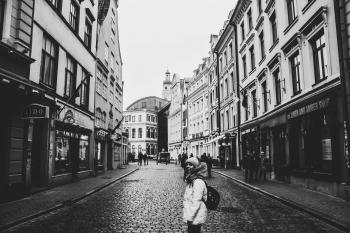 Grayscale Photo of a Woman Between Buildings Photo