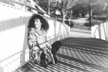 Grayscale Photo of a Woman Sitting Beside a Rail