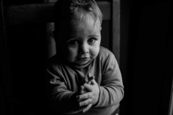 Grayscale Photo of Baby Sitting on Chair