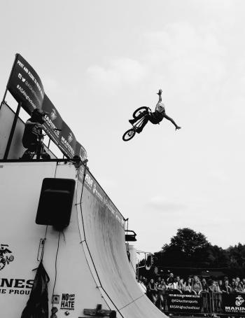 Grayscale Photo of Bmx Rider on Tournament
