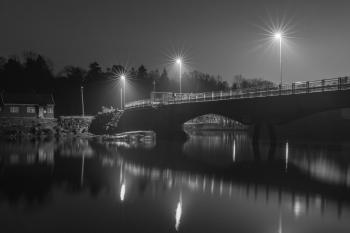 Grayscale Photo of Bridge at Night