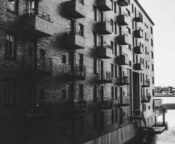 Grayscale Photo of Building Beside Body of Water