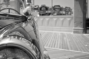 Grayscale Photo of Car Near Glass Panel