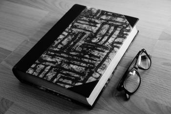 Grayscale Photo of Eyeglasses Near Thickbound Book