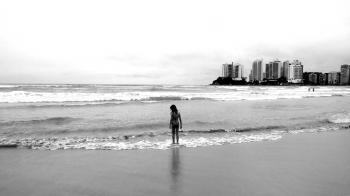 Grayscale Photo of Female Standing Seashore