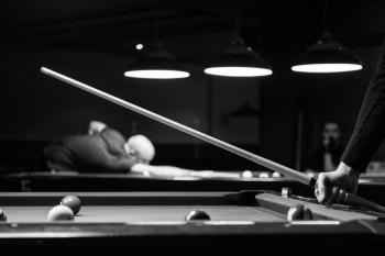 Grayscale Photo of Man Holding Cue-stick