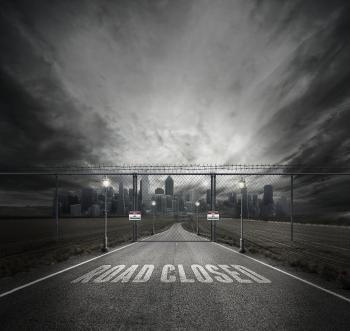 Grayscale Photo of Road Closed on Roadway With Gray Fence Gate in Front of City
