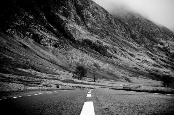 Grayscale Photo of Road Thru Mountain