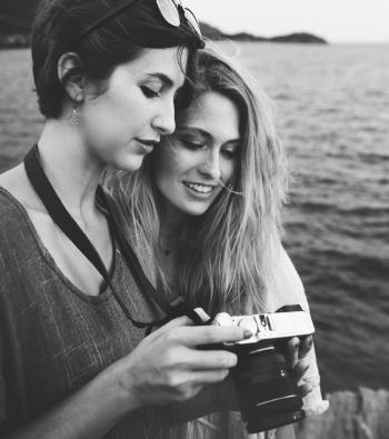 Grayscale Photo Of Two Women Looking At A Camera