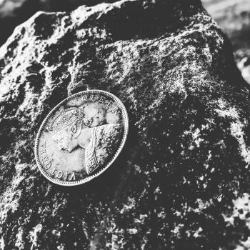 Grayscale Photo of Victoria Queen Coin on Top of Rock