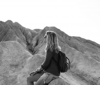 Grayscale Photo of Woman Sitting on Rock