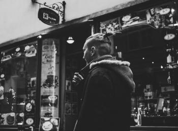 Grayscale Photograph of Man Walking Past by Shop