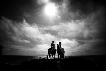 Grayscale Photography of Couple Riding on Horse With Body of Water and Sky As Background
