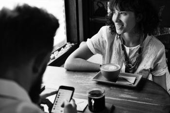 Grayscale Photography of Man and Woman Sitting Beside Wooden Table