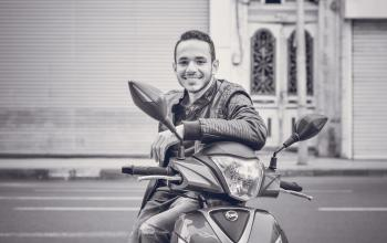 Grayscale Photography of Man Sitting on Motorcycle