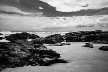 Grayscale Photography of Rocks on Seashore during Daytime