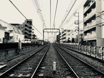 Grayscale Photography of Train Rail Between Buildings