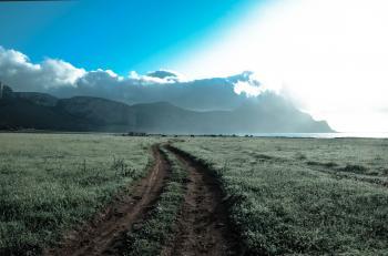 Green Grass Field Beside Brown Mountains Under White Cloudy Sky