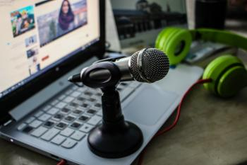Green Headphones Near Laptop and Microphone