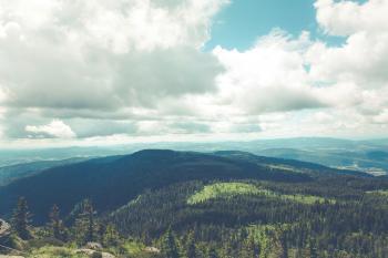 Green Hills Below White Cloudy Sky