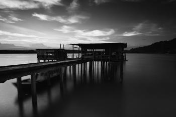 Greyscale Photo of Dock Near Mountains