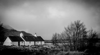 Greyscale Photo of House Within Mountain Range