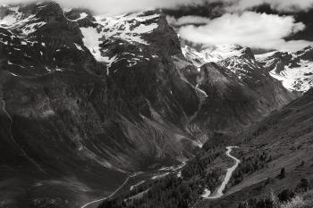 Greyscale Photo of Mountains Surrounded by Clouds
