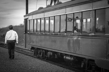 Greyscale Photography of Train Beside Woman