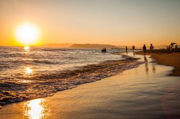 Group of People Walking at the Shoreline during Golden Hour