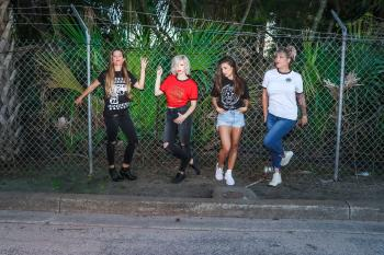 Group of Women Standing in Front Metal Fence