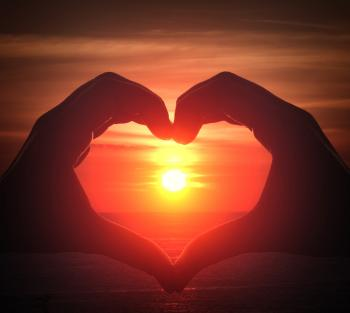 Hand silhouette in heart shape with sunset in the middle