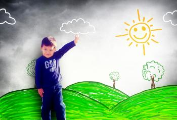 Happy child drawing a sunny landscape