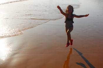 Happy girl jumping on the beach at dawn