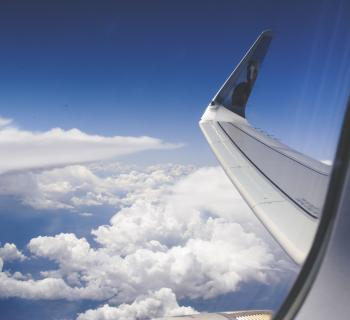 High-angle Photograph of Airplane Wings Above the Clouds Under Clear Blue Sky