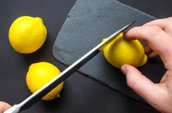 Human Slicing Yellow Lemon
