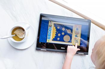 Kid Using Black Dell Tablet With Tea