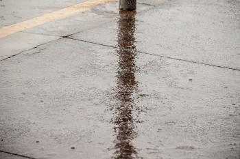 Lamp post reflection on rainy ground