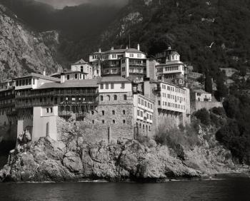 Landscape Photography of Gray and White House Near Mountain Cliffs Above Body of Water